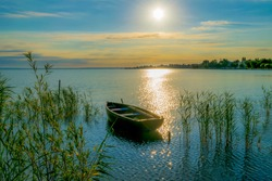 Rowing boat on lake at sunset Small wooden rowing boat on a calm lake at sunset reed