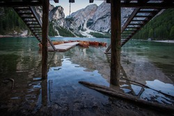 Rowing boats moored under a pair of wooden stairs in an idyllic setting with dolomitic mountain background, Braies Lake, South Tyrol, Italy. Concept: relaxation in nature, famous natural places