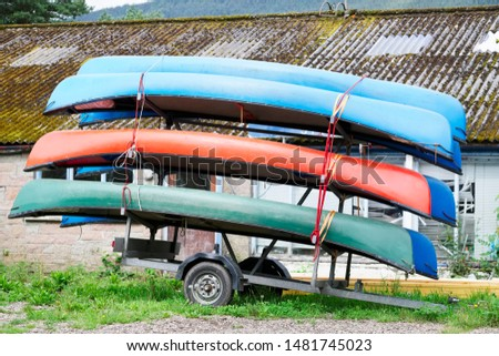 Rowing canoes stacked on trailer for transport to lake