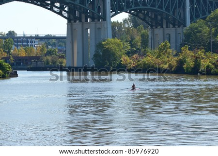 Rowing On The River :  A man rows his boat inland on the winding Cuyahoga River at Cleveland, Ohio