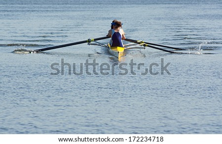 Rowing team working in unison to compete in a regatta by racing specially built row boats