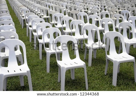 rows and columns of white mono-block chairs