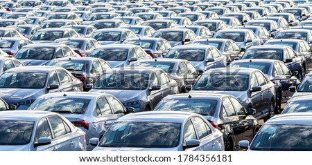 Rows of a new cars parked in a distribution center on a car factory on a sunny day. Top view to the parking in the open air.
