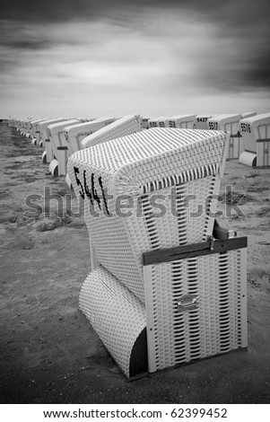 Rows of abandoned roofed wicker beach chairs at a beach in black and white