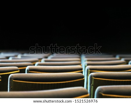 Rows of armchairs in a theater or cinema, back view. Dark background