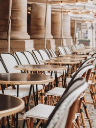 Rows of black coffee tables and white wicker chairs on a Parisian street. An ideal place for a typical Parisian breakfast in cafe.