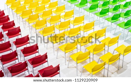 Rows of bright color chairs arranged in meeting room ready to sit. high angle shoot, top view photo. #1129220909