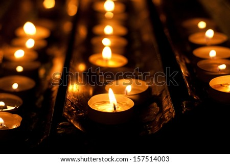 Rows of brightly burning votive candles
