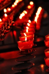 Rows of burning candles inside a cathedral in the dark