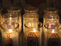 Rows of burning Catholic prayer candles, with St. Jude and Mary, glow in darkness inside Mission San Xavier Del Bac, a National Historic Landmark and an active parish in Southern Arizona