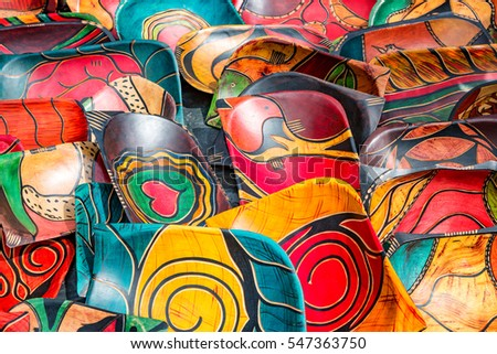 Rows of carved, hand painted wood bowls. Hand crafted souvener giftware, with colourful tribal designs, at a market in South Africa.