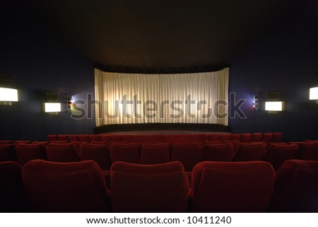 Rows of chairs in a cinema with the curtain drawn