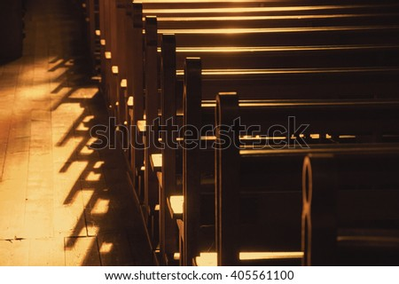 Rows of church benches. Sunlight filtered through the stained glass window. Selective focus. Sepia photo.