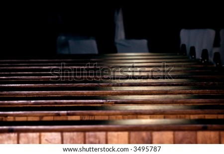 Rows of church pews with stream of light
