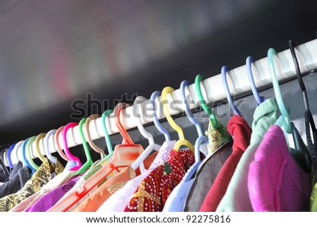 Rows of colorful clothes hanger in wardrobe.