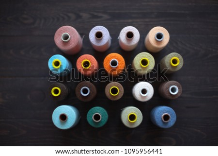 Rows of colourful bobbins with threads on a wooden background - Shutterstock ID 1095956441