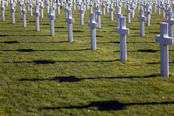 Rows of crosses with long shadows at the American Cemetery and Memorial near Luxembourg in Europe