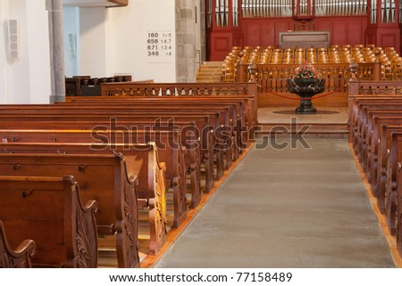 rows of decorated wooden church benches on both sides of the aisle with flower decoration and choir