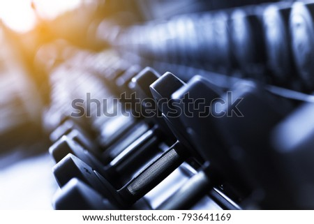 Rows of dumbbells in the gym. monochrome color tone and glare of the sun