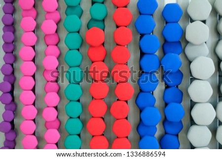 Rows of dumbbells of different colors and shapes are stored in a special rack made of strong metal. Diamond-shaped dumbbells background for fitness. Background of dumbbells of different color and size