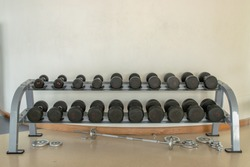 Rows of dumbbells on a rack in the fitness or gym. Weight Training Equipment. Copy space, Selective focus.