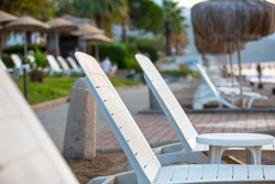 Rows of empty beach loungers and parasols await holidaymakers on the seashore. Selective focus, blur. Beautiful image of the resort