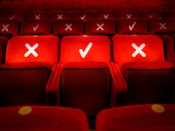 rows of empty chairs in a theater with the indication of where it is possible to sit to maintain the social safety distance during the period of the COVID-19 corona virus pandemic. Social distancing