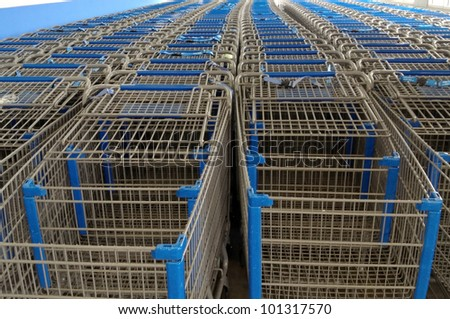 Rows of empty metal shopping carts with blue handles and accents