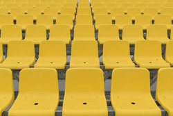 Rows of empty place in the stadium. Plastic seats in yellow.