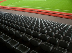 Rows of empty seats in a soccer sports stadium with green grass. Seen from above.