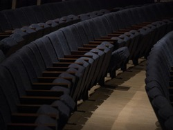 Rows of empty theater seats, in a dark auditorium.  Most seats are folded up, some remain lower.  Blue fabric, concrete floor, dark interior shot of performing arts center.