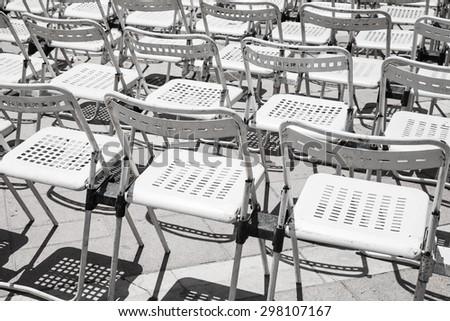 Rows of empty white metal chairs in an open-air concert hall