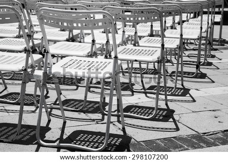 Rows of empty white metal chairs in an open air concert hall
