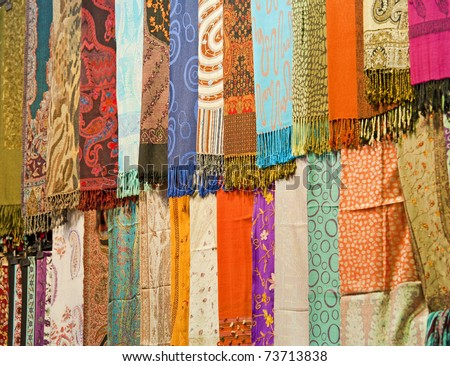 Rows of fabrics hanging at a market stall
