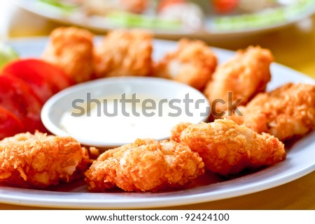 Rows of freshly cooked crab cakes for sale at a street market - stock photo