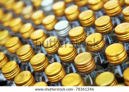 Rows of golden color bottle caps with shallow depth of field