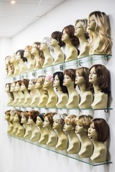 Rows of hair wigs on display, on some dummies, in a store.