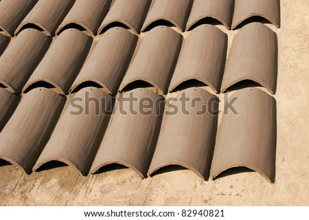 Rows of handmade clay roofing tiles drying in the sun