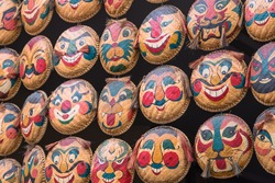 Rows of hanging face painted on woven round bamboo trays. Famous colorful straw tray masks art in Hanoi, Vietnam. Multi-faces ancient souvenir are sales in many shops around downtown and old quarter.