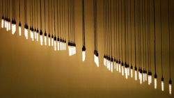 Rows of hanging pendant lights on long wire strings with yellow brown background. Glowing light bulbs hanging in diagonal row on blurred backdrop with copy space. Industrial style lamps.