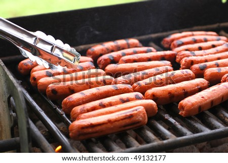 rows of hot dogs on barbeque grill at park stock photo