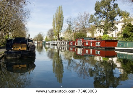 Rows of houseboats and narrow boats on the canal banks at Little Venice, Paddington, West London.  The Grand Union Canal meets the Regent's Canal here. - stock photo