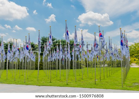 Rows of Korean flags on chrome flagpoles in green lawn next to concrete plaza. #1500976808