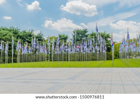 Rows of Korean flags on chrome flagpoles in green lawn next to concrete plaza. #1500976811