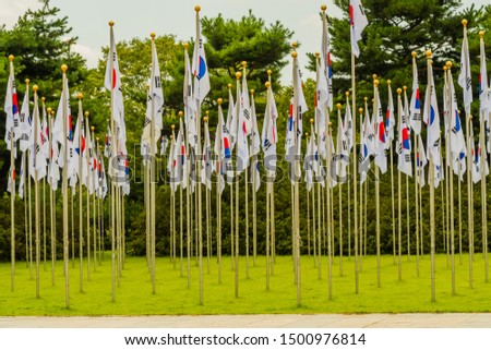 Rows of Korean flags on chrome flagpoles in green lawn next to concrete plaza. #1500976814