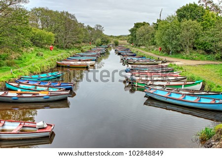 Rows of little multicolored rowing boats are moored on Lough Leane (Lower Lake) Killarney, Ireland,