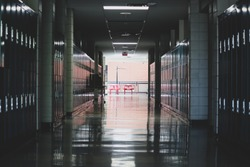 Rows of lockers dipped in shadow with a single bright lit window at the end of the hallway