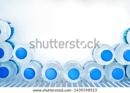 Rows of many transparent plastic bottles with drinking water supply in white refrigerator. Mineral water stack storage in fridge to drink on hot summer day. Healthcare and dehydration prevention