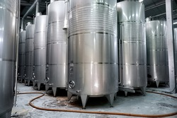 Rows of metal wine storage tanks located in winery