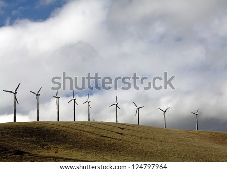 Rows of modern windmill in an energy wind farm on top of a hill against a dramatic cloudy sky.